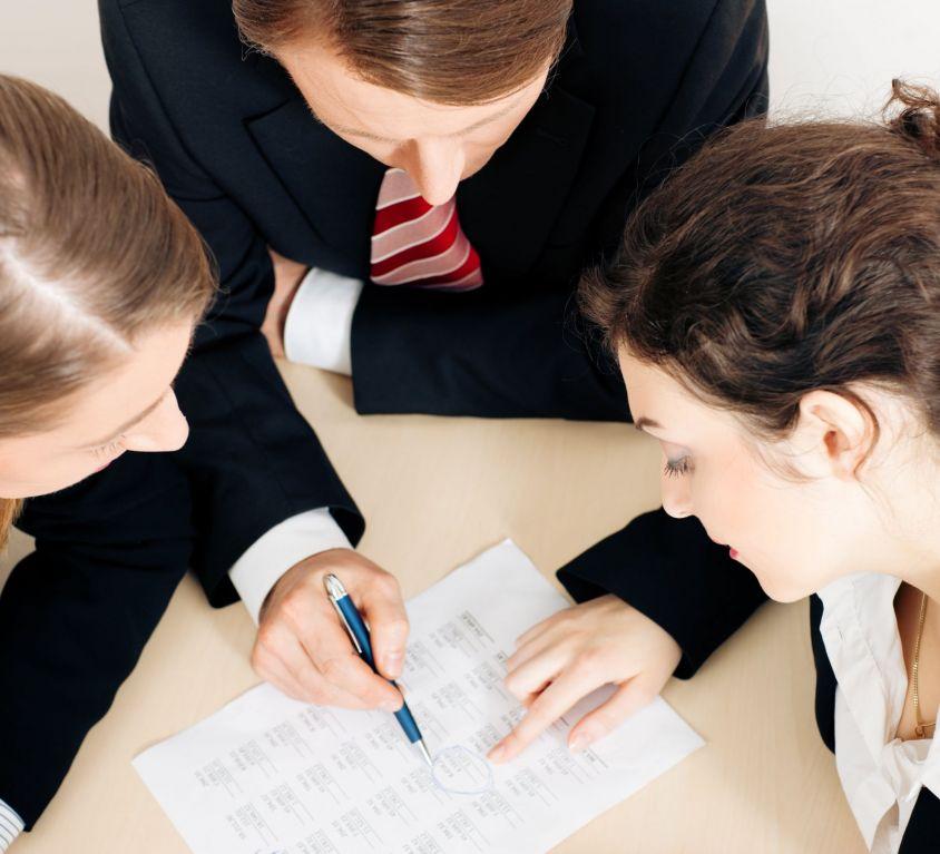 Colaboradores com ternos apontando para um documento, trabalhando em conjunto para simbolizar o engajamento da força de trabalho